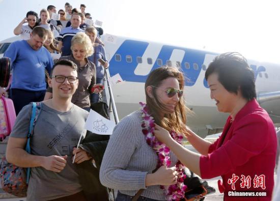 资料图:去往海南旅游的游客受到热烈欢迎。<a target='_blank' href='http://www.chinanews.com/'></table>中新社</a>记者 尹海明 摄