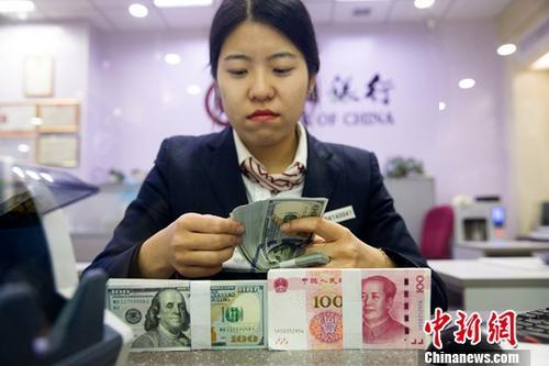 12月14日,山西太原,银行工作人员清点货币。当日,来自中国外汇交易中心的数据显示,人民币对美元汇率中间价报6.6033,较前一交易日上涨218个基点。<a target='_blank' href='http://www.chinanews.com/'></table>中新社</a>记者 张云 摄