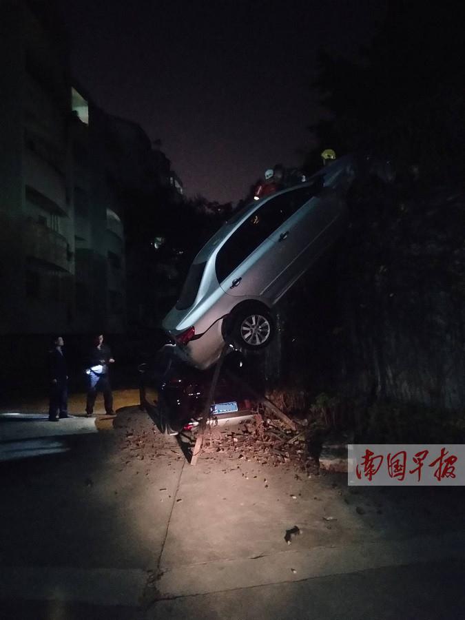 女司机倒车操作失误撞破路边围挡 车高挂墙上(图)