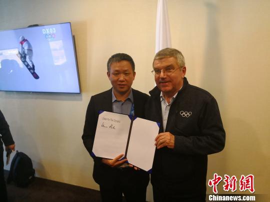 """国际奥委会主席巴赫在印有""""为奥运喝彩""""英文字样的纸上签上了自己的名字,表达了他对这一奥运文化项目的支持 """"为奥运喝彩""""项目组供图"""