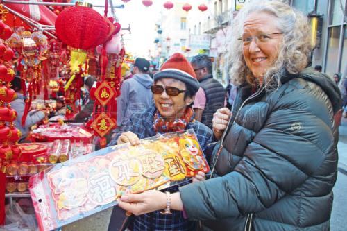 """美国非华裔民众也在选购年货,拿着""""福来旺到""""的春联。(美国《世界日报》记者李晗/摄影)"""