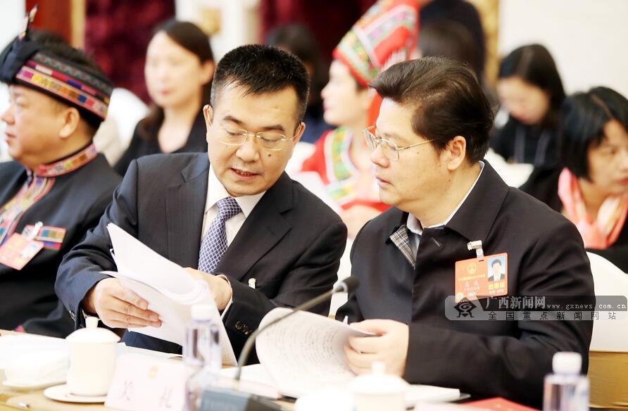 3月14日,广西代表团举行全体会议审议国务院机构改革方案。何良军代表与关礼(右)代表在审议时交流意见