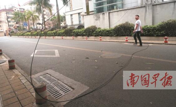 线缆被刮倒掉落地面 环卫女工守在现场提醒避让