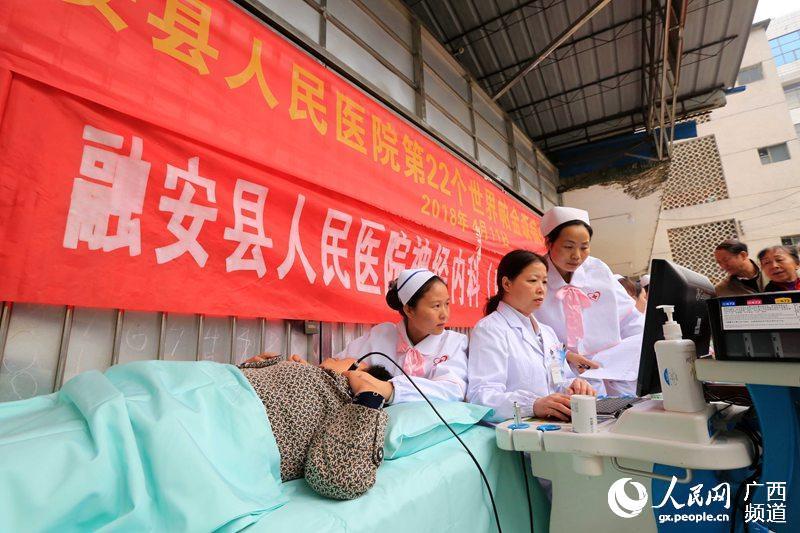 4月11日,广西柳州市融安县政府大院,医护人员在为老人免费进行颈部动脉多普勒超声检查(谭凯兴/摄)