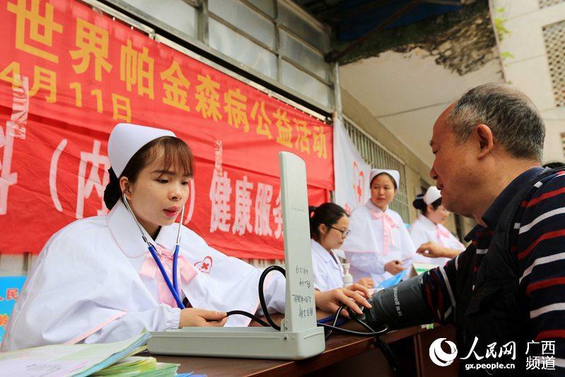4月11日,广西柳州市融安县政府大院,一名南丁格尔志愿者在为老人测量血压(谭凯兴/摄)