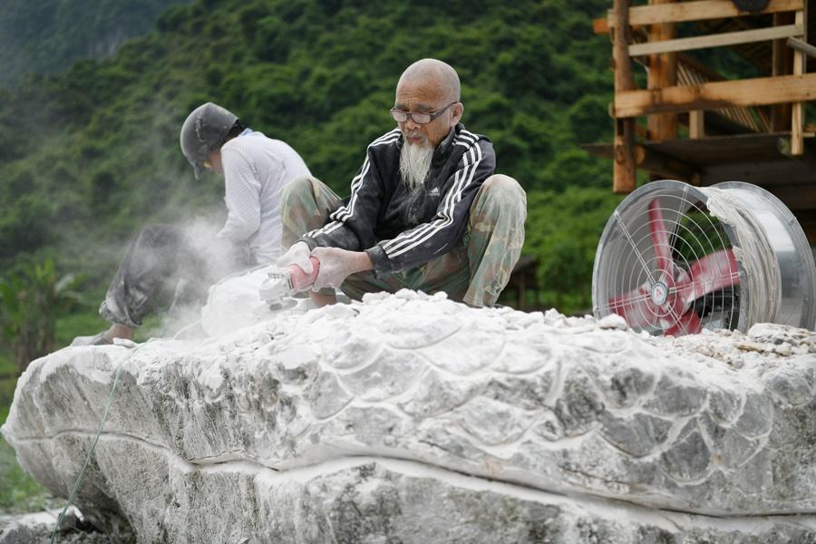 """88岁民间艺人把仫佬族""""非遗""""图案刻入石头(图)"""