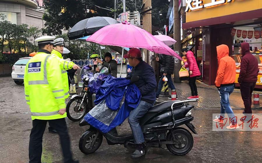 """危险又违法 南宁交警整治电动车""""打伞""""行为(图)"""