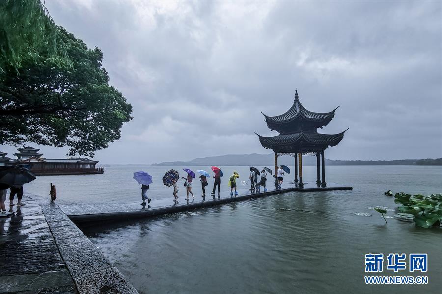 游客在风雨中foganglao佛冈门户网观赏西湖(手机拍摄)