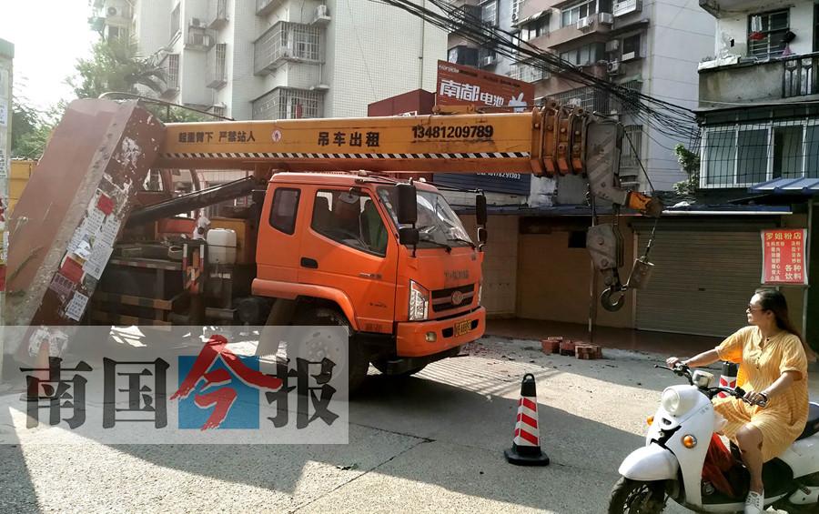 柳州:吊车撞上限高杆 带塌市场大门柱动弹不得