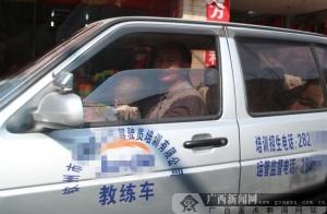 钦州一教练车司机怀抱幼儿开车
