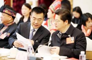广西代表团举行全体会议审议国务院机构改革方案。何良军代表与关礼(右)代表在审议时交流意见