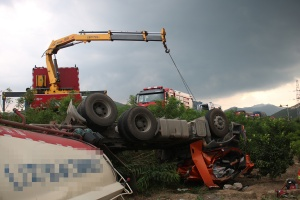 永福:水泥罐车翻下路基 柴油泄漏司机身亡(组图)