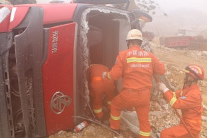 河池一大货车侧翻致一人被困 消防雾中救出被困者