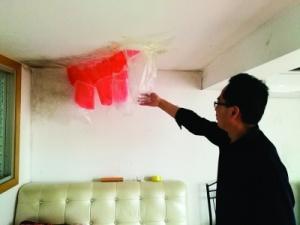 一居民楼的墙面渗水严重,住户只能粘塑料袋接水