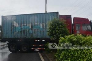 钦州:雨天路滑车辆失控 大货车冲上花带动弹不得