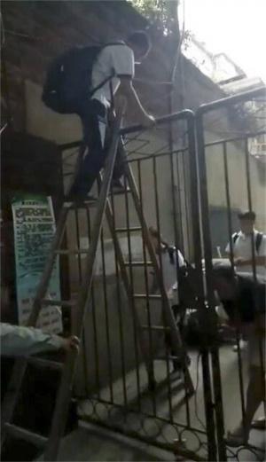 咋回事?一群孩子紛紛爬梯翻過大門去上學