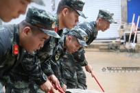 广西环江:武警驰援受灾乡镇清理淤泥(图)