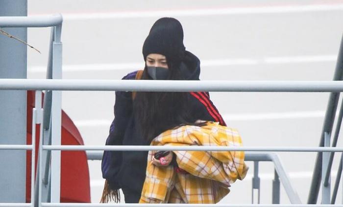 杨幂怀抱外套再现机场神情严肃