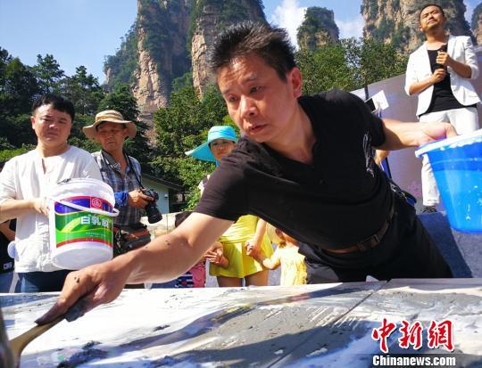 土家族画家创作百米砂石画长卷绘制张家界风光