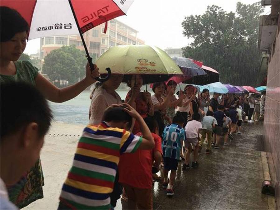 """温情:大雨中老师接力为孩子们撑起""""彩虹桥""""(图)"""