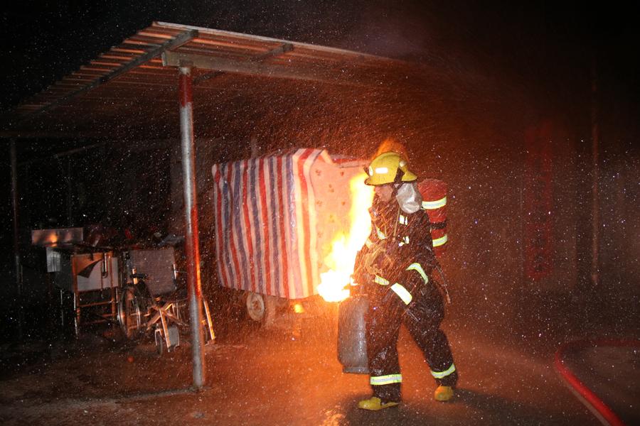 南丹一居民楼起火 消防员火场中转移燃烧的煤气罐