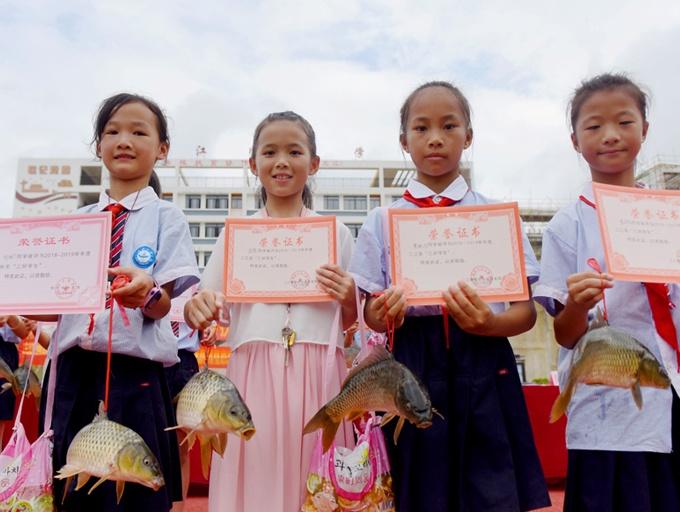 高清:广西三江一小学奖励考试获奖学生活鲤鱼