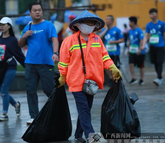 一名清洁工提着两袋垃圾前去处理