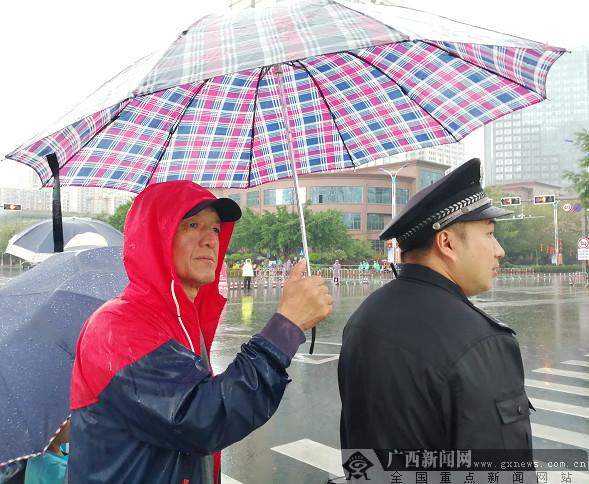一名观众为不穿雨衣的值勤民警打伞