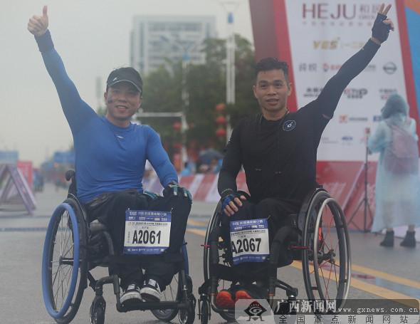 两名残疾选手冲过全马终点后挥手庆祝